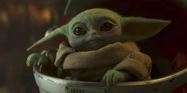 Baby Yoda rides in his baby stroller