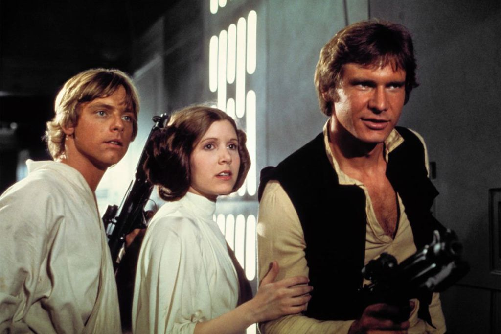 Luke, Leia, and Han pause in the hallway, blasters drawn